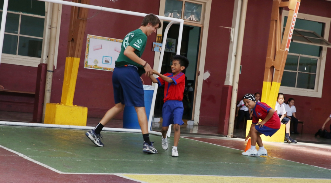 A volunteer runs with a kid during practice on the sport volunteering project in Costa Rica